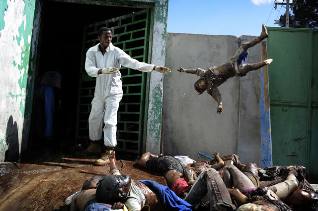 1st Prize General News Stories: Olivier Laban-Mattei, France, Agence France-Presse. Haiti earthquake aftermath, 15-26 January. A man throws a dead body at the morgue of the general hospital, Port-au-Prince, 15 January