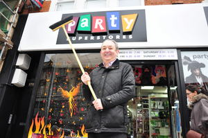 Duncan Mundell celebrates with a broom now his store has reopened almost two years after it was burned during the riots