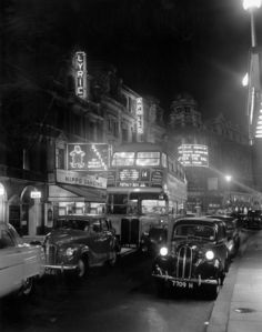29th September 1954:  A bus and cars travelling down Shaftesbury Avenue, London, in front of an illuminated Lyric Theatre, at night.  (Photo by Monty Fresco/Topical Press Agency/Getty Images)