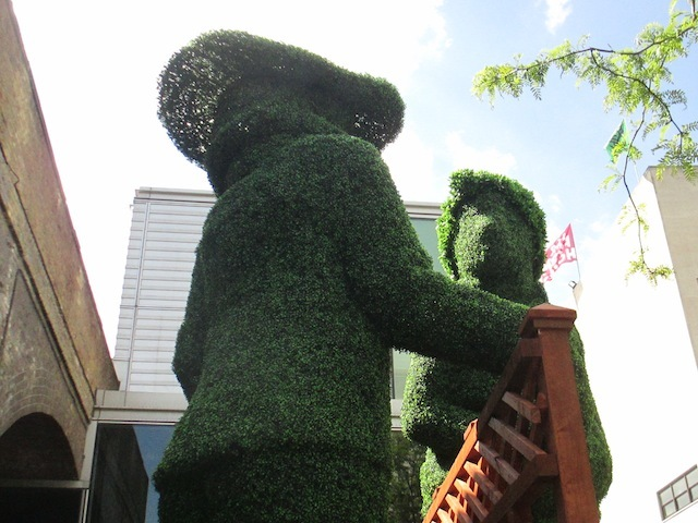 Giant topiary figures bookend the site.