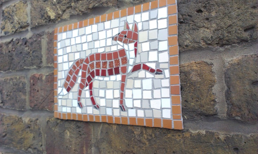 Crafty fox mosaic panel on St. Matthew's Hosptal (79 Shepherdess Walk) points the way to Shepherdess Walk Park and its Mosaics