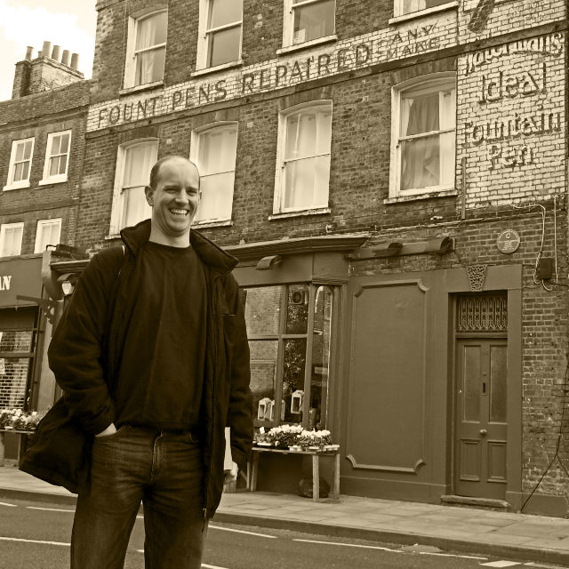 Sam Roberts in front of the ghost sign that inspired it all. (Photo: Gloria Soria)