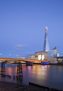 No.1 London Bridge, London, United Kingdom. Architect: John S. Bonnington Partnership, 1986. View of the offices looking across the river Thames  with the Shard in the background and London bridge lit up in the foreground. Ancient river wharfs are visible at low tide to the bottom of the picture.