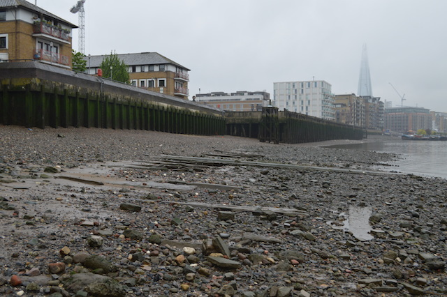 Rotherhithe, looking west at low tide. Old ship timbers line the foreshore. Chambers Wharf, in the distance, stands over ancient peat beds, which indicate a small island or eyot was once sited here.