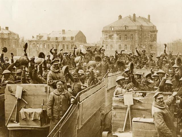 Photo - cheering troops on the top decks of converted B-type buses, in a square at Arras, France, 1917