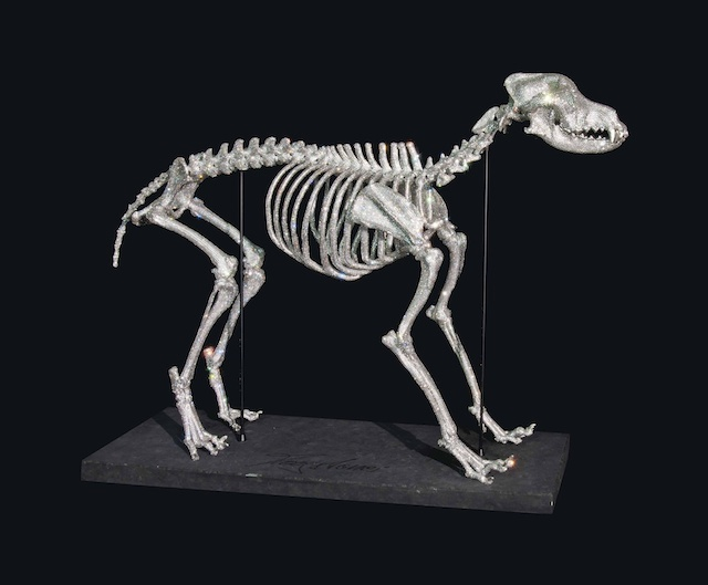 A Swarovski crystal-encrusted skeleton of a dog (canis lupus familiaris).  The teeth and claws have been applied with platinum, and the skeleton is held in place with magnets, set on a stone plinth with carved inscription 'Moogstones' , with a fitted box. (Estimate £20,000-£30,000)