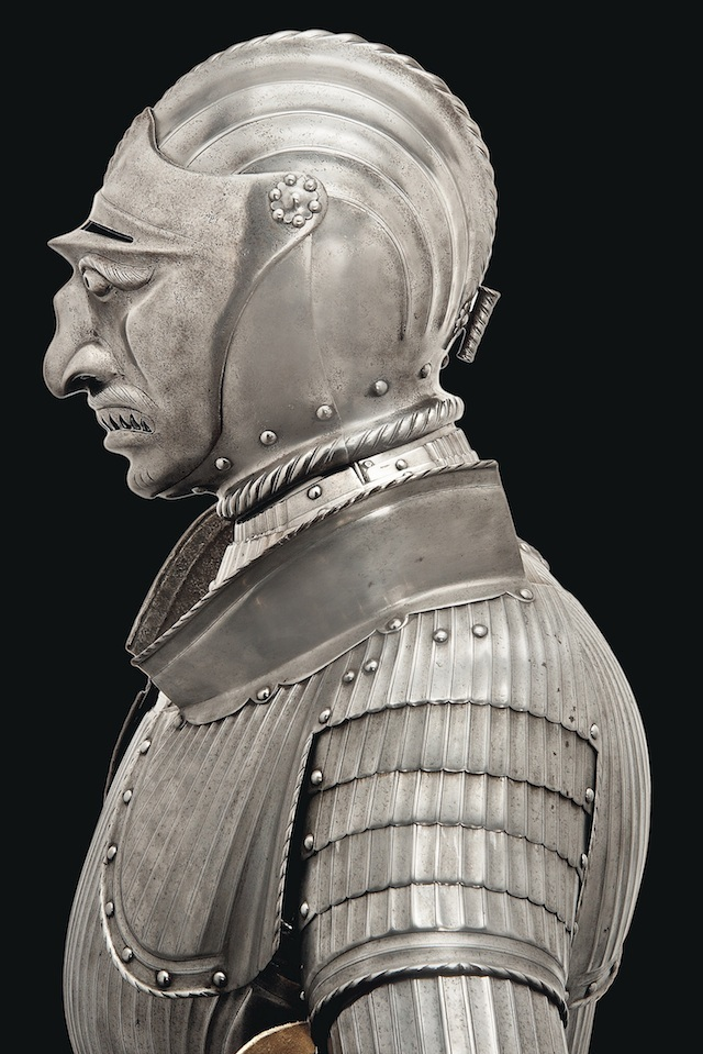 An  imposing decorative full armour with grotesque visor, in German early 16th century Maximilian style. Made during the second half of the 19th century out of bright steel with characteristic fluted decoration throughout. It includes a close-helmet with twin roped combs and pivoting visor with fierce countenance of barred teeth, hooked nose and bulging eyes. (Estimate £25,000-£30,000)