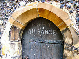 Commit No Nuisance sign on clock tower door