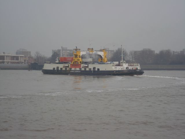 The Woolwich Ferry trundling between banks of the Thames