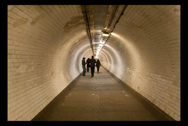 The Pattersonians walk beneath the Thames in the Greenwich Foot Tunnel. By Brett.
