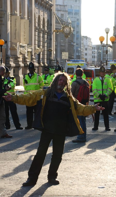 A protester does a little dance for the camera while police look on / image by Doilum
