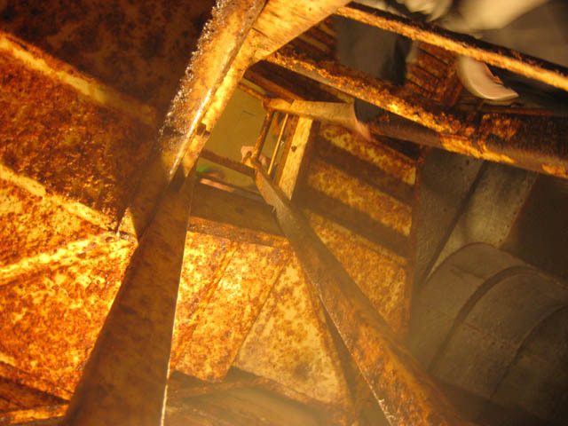 A pair of rusting spiral staircases connect the two floors.