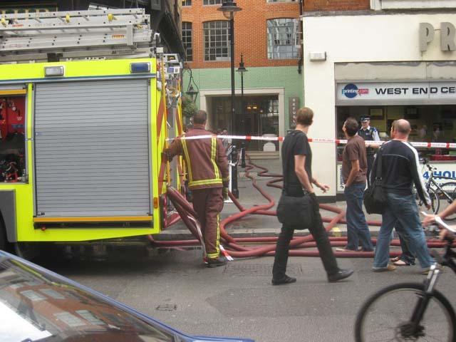 Firemen plug in hoses on Wardour Street, feeding them into the Soho Hotel's Refuel Bar.