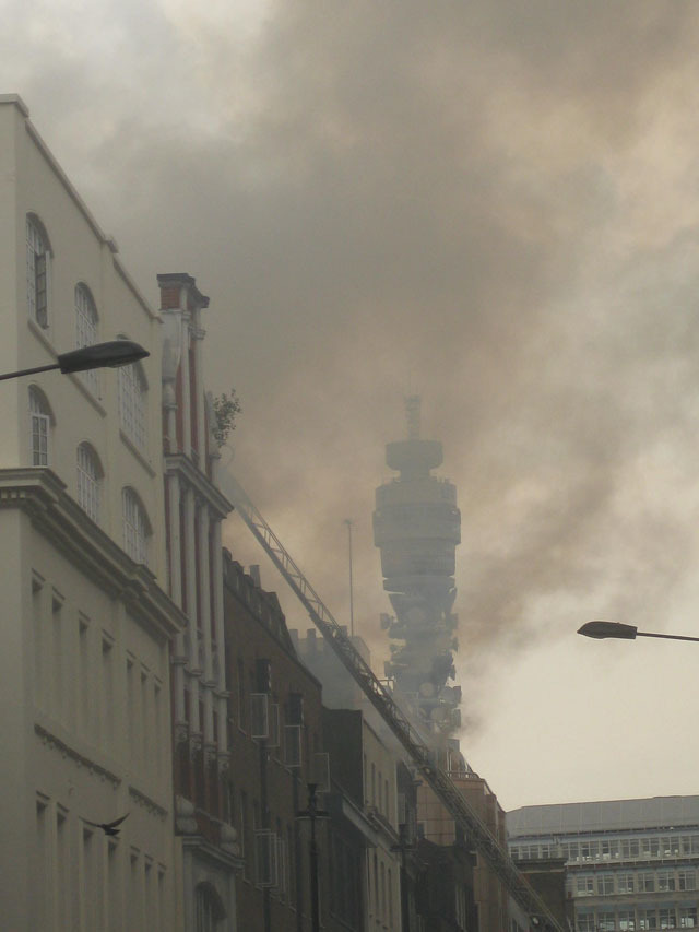 From the southern end of Dean Street, the BT Tower appears shrouded in smoke.