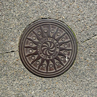 Sun motif on a coal hole cover in Goldsmith's Row, E2