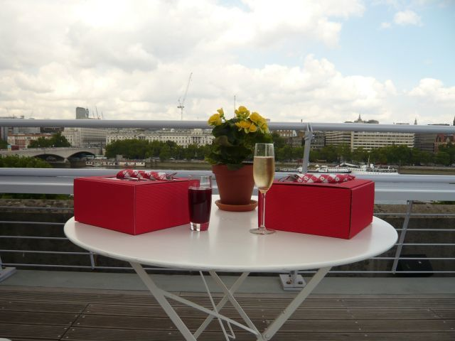 Picnic boxes and champagne, view of London behind. Photo by W P Wiles