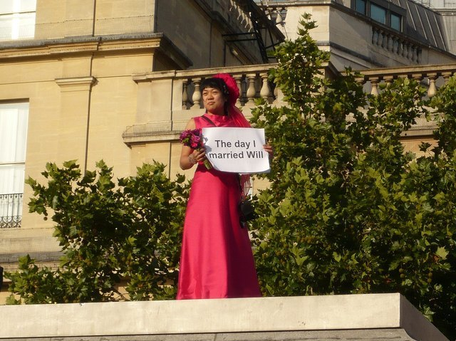 Holding banner no. 3 with description explaining my re-enactment: 'The day I married Will'. Photo by W P Wiles