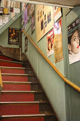 The stairs to the basement, lined with posters of current shows and a few prints for sale