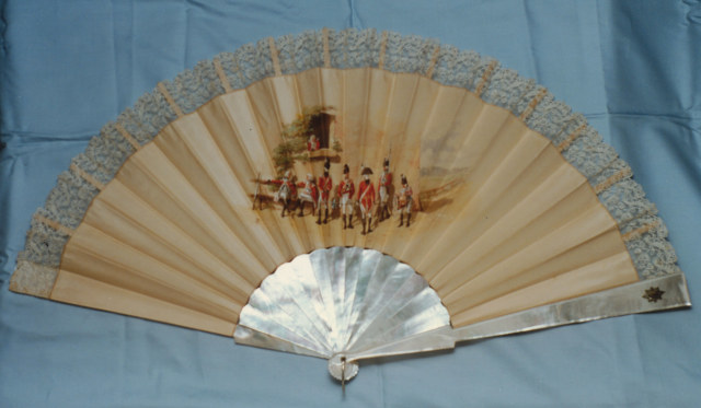 Mother-of-pearl fan with silk leaf edged in lace painted by R. Wymer with a group of Coldstream Guards at rest. English, late 19th century