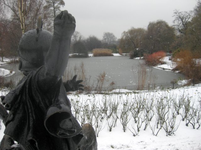 A statue appears to hurl a snowball at a frozen pond in Regent's Park.  M@