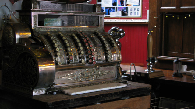 The original Victorian cash register still in use in the pub. Various elements of the theatre such as lamps and the red velvet curtains have been recycled from other famous West End theatres.