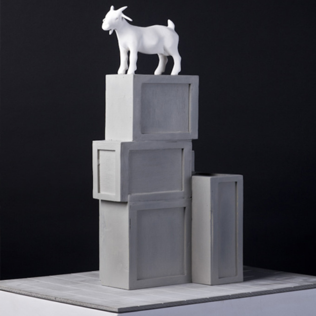 By Kenny Hunter. It's a goat. On a plinth. Take that, Antony Gormley. The crates represent the waves of migration into this quarter.