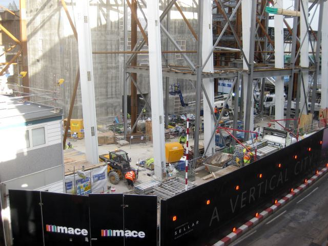 Looking down at the base of construction. Giant steel beams rise from the basement.