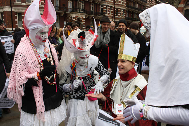 Sisters of the London House of Common Sluts of the Sister of Perpetual Indulgence officiate on a disguised protestor.