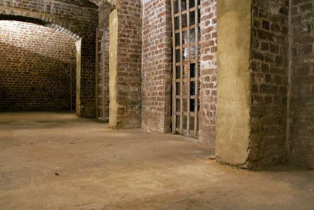 The entrance room contains a number of holding cells, given replica wooden doors by a recent production.