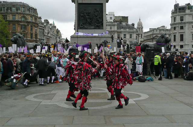 Morris Men doing their thing, with protesters doing their thing in the background. Photo by Dave.