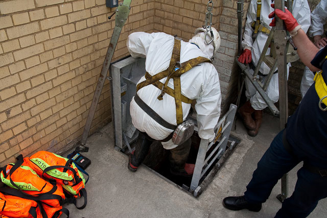 Wearing a safety harness a sewer worker prepares to descend. Note the orange bags - these contain emergency oxygen supplies and must be carried by all visitors.