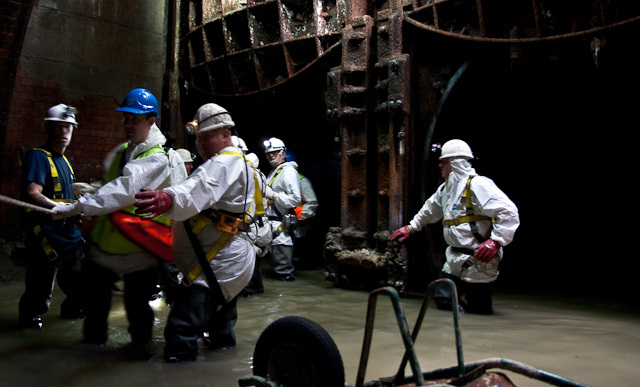 The group pauses inside a chamber, thigh-deep in effluent.