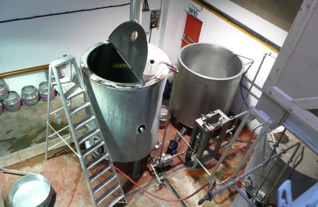 Various vessels as seen from the malt loft: a 'copper' in the centre, hot and cold 'liquor tanks' to the right and an 'underback' to the lower left. A heat exchanger is mounted between the liquor tanks and the copper. Photo by Dave