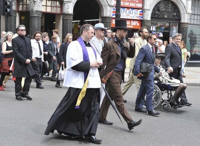 Formal attire in the funeral procession, including great hats