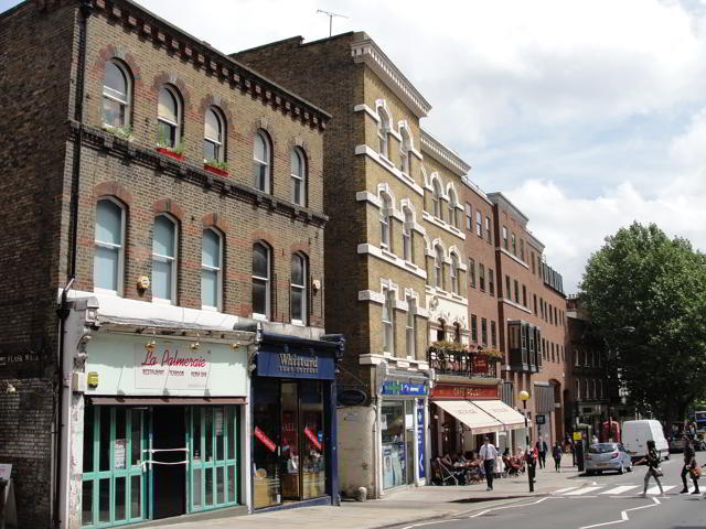 """Hampstead High Street: """"And the shops were busy, doors open, inviting, whilst the mortals inside them paid homage to their other great object of worship - money. No wonder Hermes was always working."""" p.68"""