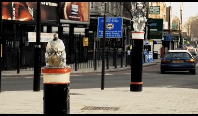 A Credit Crunch Monster at Aldgate is eyed up by one of the City's traditional guardians.