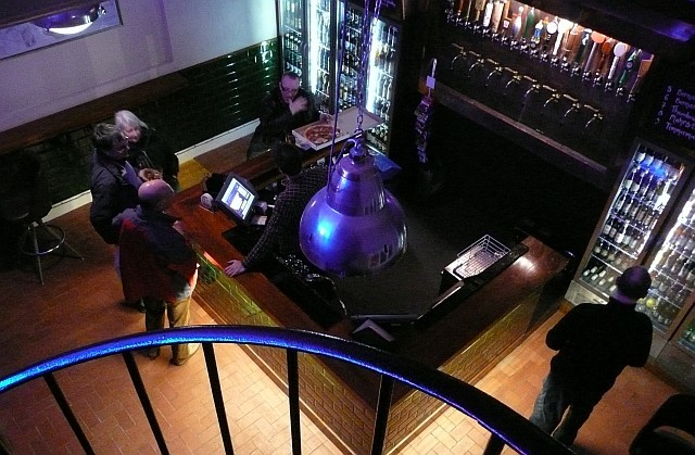 The ground floor of the Euston Tap, as seen from the top of the spiral staircase. Photo by Dave.