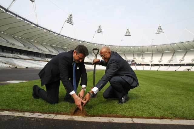 Former Olympian Frankie Fredericks and Seb Coe lay the final piece of turf yesterday. Photo by David Poultney.