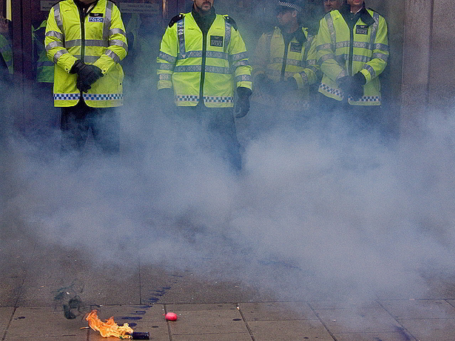 A burning missile thrown towards police outside TopShop / chrisjohnbeckett from the Londonist Flickr pool