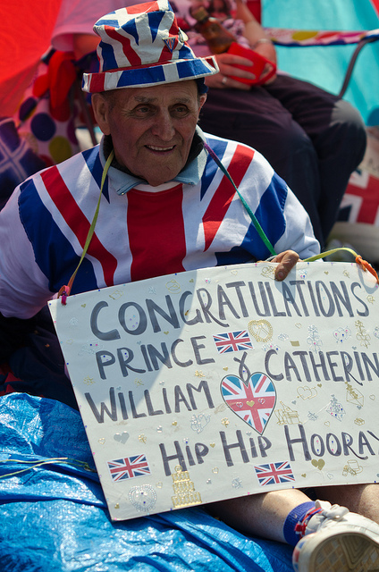 One of the older members of the Royal Campsite in Westminster displays a sign congratulating the happy couple. The area around Westminster Abbey on the eve of the Wedding of Prince William and Catherine Middleton; Where members of both the media and public have set up camp to get the best view of the couple as they leave the Abbey as husband and wife. Royal Wedding. Westminster Abbey, Westminster, London. Kris Wood. 28/04/2011