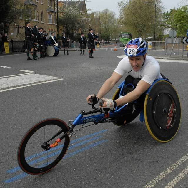 A wheelchair athlete passes through Rotherhithe with musical accompaniment from the pipe band by McTumshie