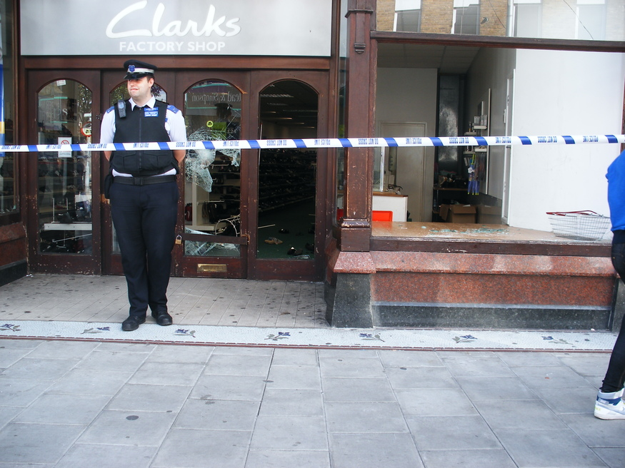 A policeman stands guard outside Clarks: no sign of any staff