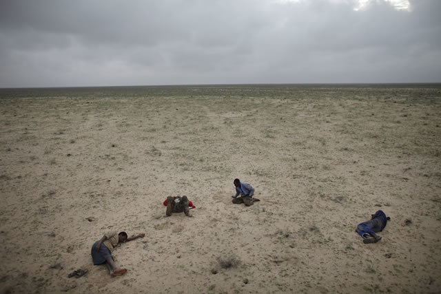 1st Prize Contemporary Issues Stories: Ed Ou, Canada, Reportage by Getty Images. Escape from Somalia, March: Four Somali refugees en route to Yemen sleep in the desert after traveling all night on muddy roads and in pouring rain, Somaliland, 15 March