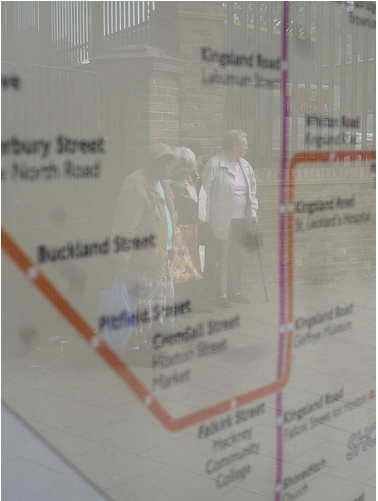 Reflection of pensioners waiting for bus, on bus map Dalston Lane, E8 by tributory