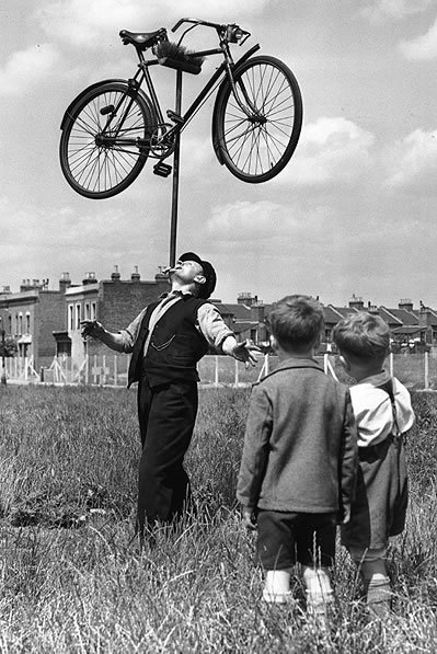 "Balancing Act: 16 August 1952: In the field outside his house in Plaistow, East London, 62-year-old railway worker Mo Harris balances a bicycle on top of a broom on his chin, watched by a couple of incredulous youngsters. Harris is known as ""the chin-up boy of Stratford"" (Photo by William Vanderson/Fox Photos/Getty Images)"