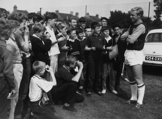 Bobby's Fans: 1 August 1962: West Ham and England captain, Bobby Moore, being photographed by young fans during a break in a training session (Photo by Douglas Miller/Keystone/Getty Images)