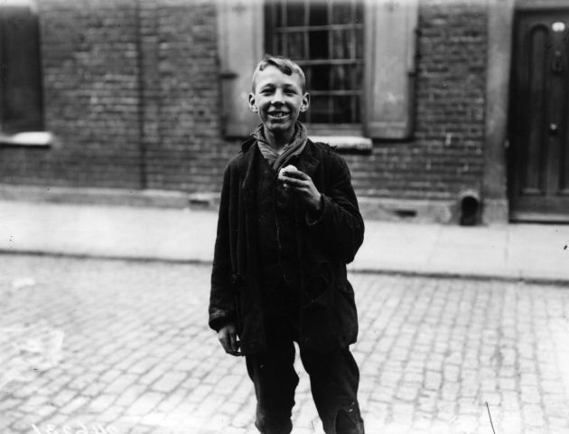 Turnip Eater: 5 July 1912: A young boy makes a meal from a turnip picked up from the road in London's East End. (Photo by Topical Press Agency/Getty Images)