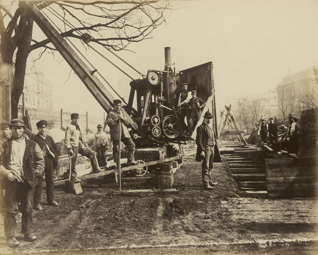 """Construction of the Metropolitan District Underground Railway, Craven Hill, Bayswater, c.1866. Photographer: Henry Flather. In Victorian times, construction work was done mainly by men known as """"navvies"""", assisted by a few primitive machines like this steam-powered crane. © Museum of London"""