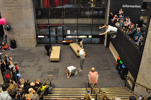 Member of Storm Freerunning leaping off the balcony in the foyer of the Barbican Centre