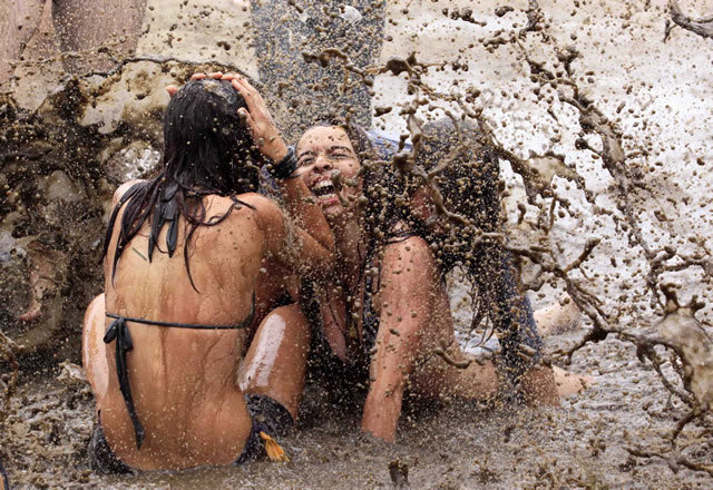 Girls enjoying the mud at the largest open-air festival in Europe: Przystanek Woodstock. It's an annual free rock music festival in Poland, inspired by and named for the Woodstock Festival